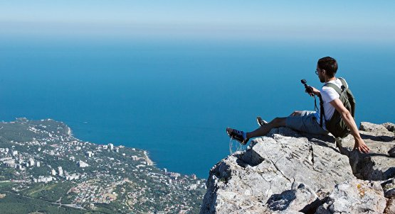 A tourist takes a photo on Ai-Petri Mountain in Crimea