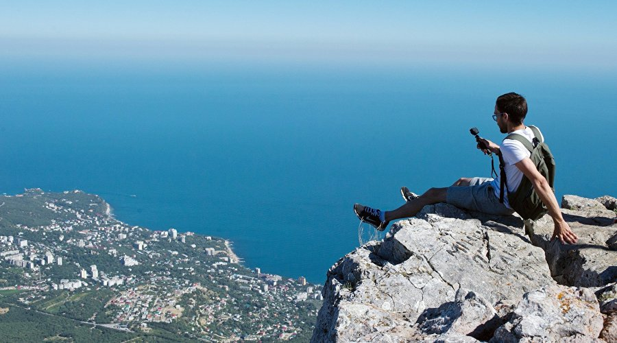 A tourist is photographed on top of the Ai-Petri mountain in Crimea